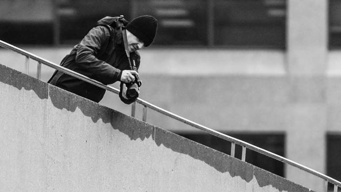 Person shooting video from the top of a staircase.