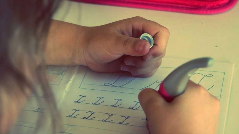 Over the shoulder shot of a child practicing penmanship.