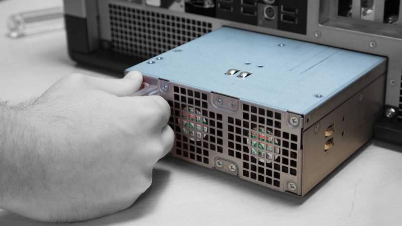 Una persona que instala una fuente de alimentación en una computadora.