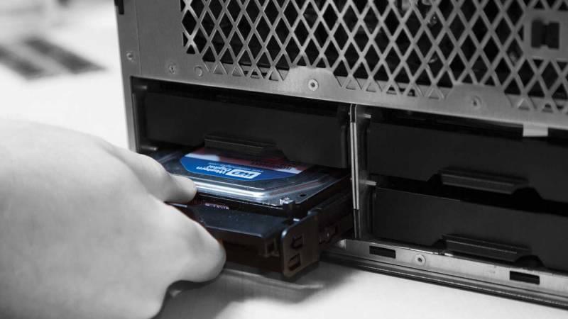 Una persona que instala una unidad de almacenamiento en una computadora.