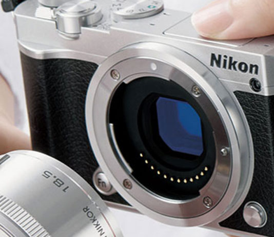 Image of the Nikon 1 J5 being held and having a lens attached to it