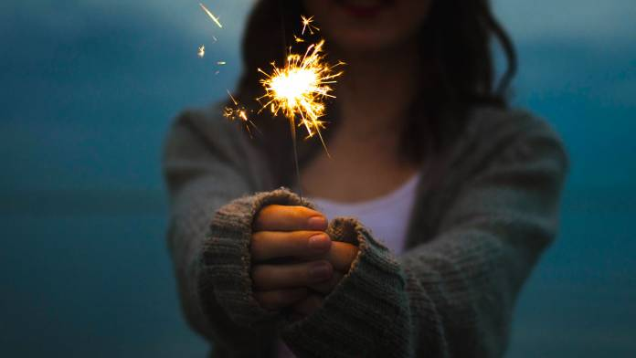 Person holding a sparkler to light a night scene.