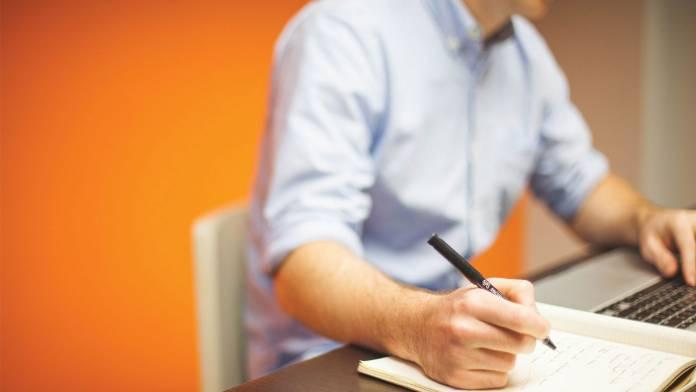 Hombre trabajando en la computadora y tomando notas