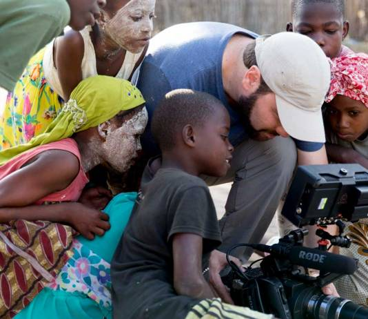Cameraman shooting with children looking at viewfinder