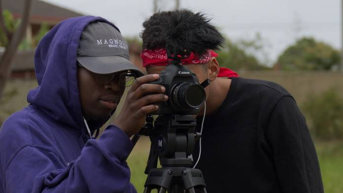 two young men stand behind a canon dslr on a tripod