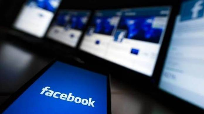 Phone in front of screens, all display Facebook