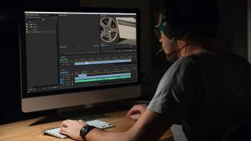 Editor working in Premiere Pro on computer