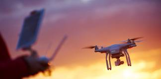 Drone operator flying drone during a sunset