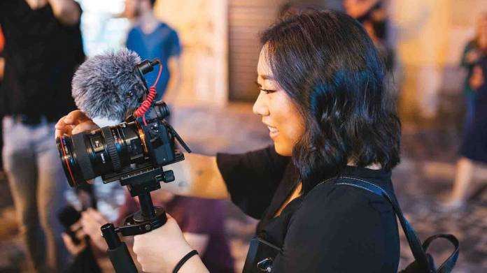 woman with camera on a small tripod with a microphone on top