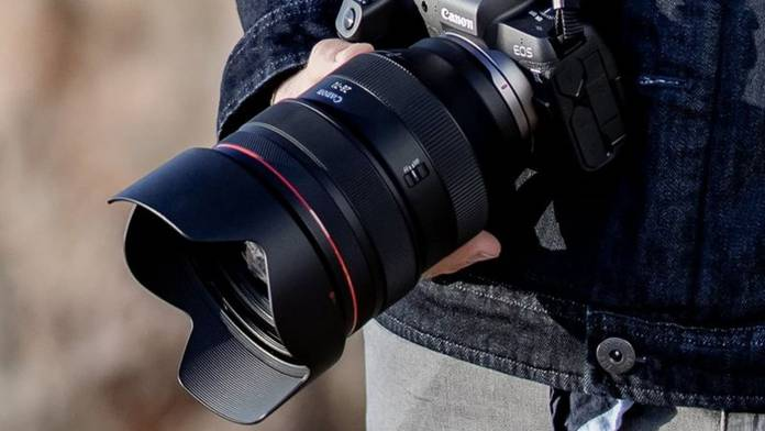 EOS R lens attached to camera body being held