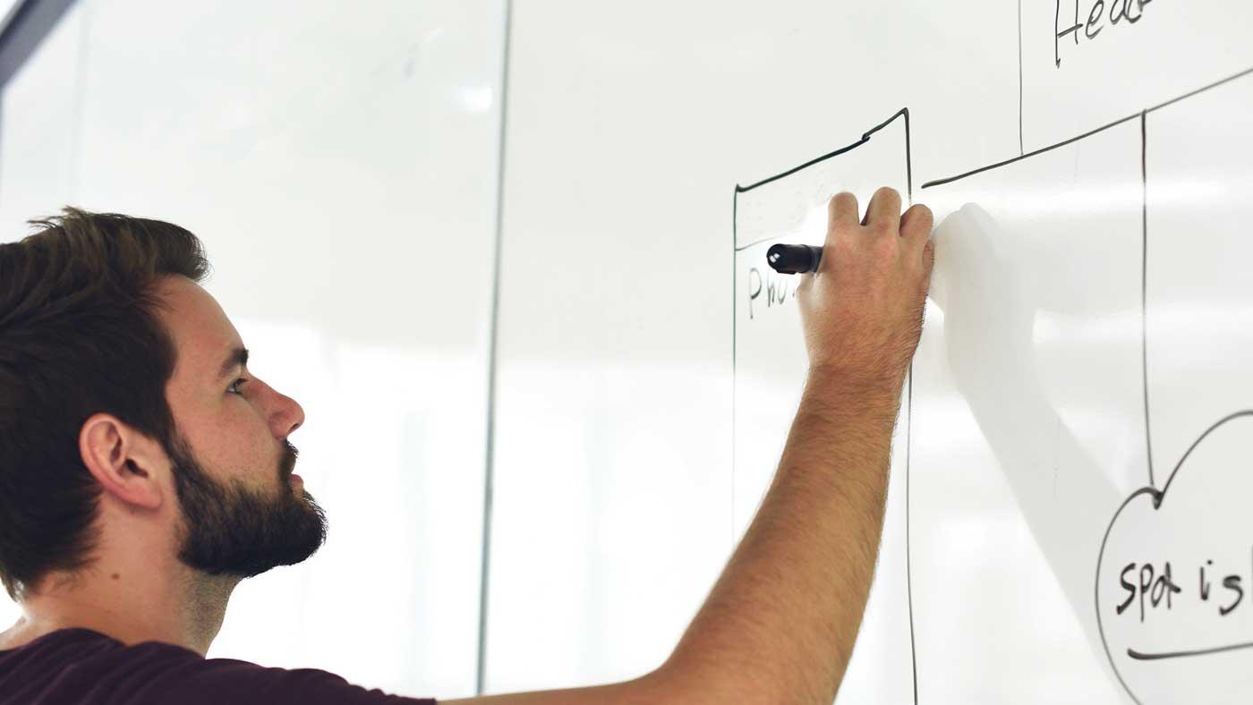 Man writing on white board.