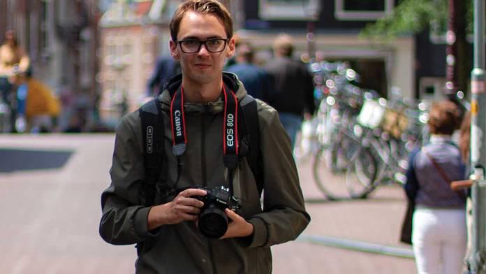 Man with camera in urban setting.