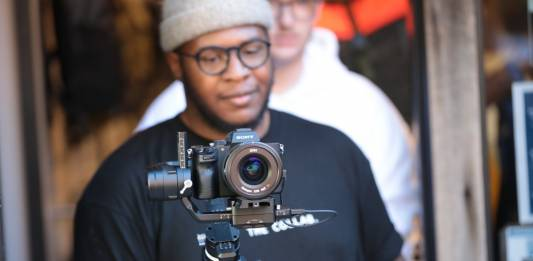 photo of man holding digital camera
