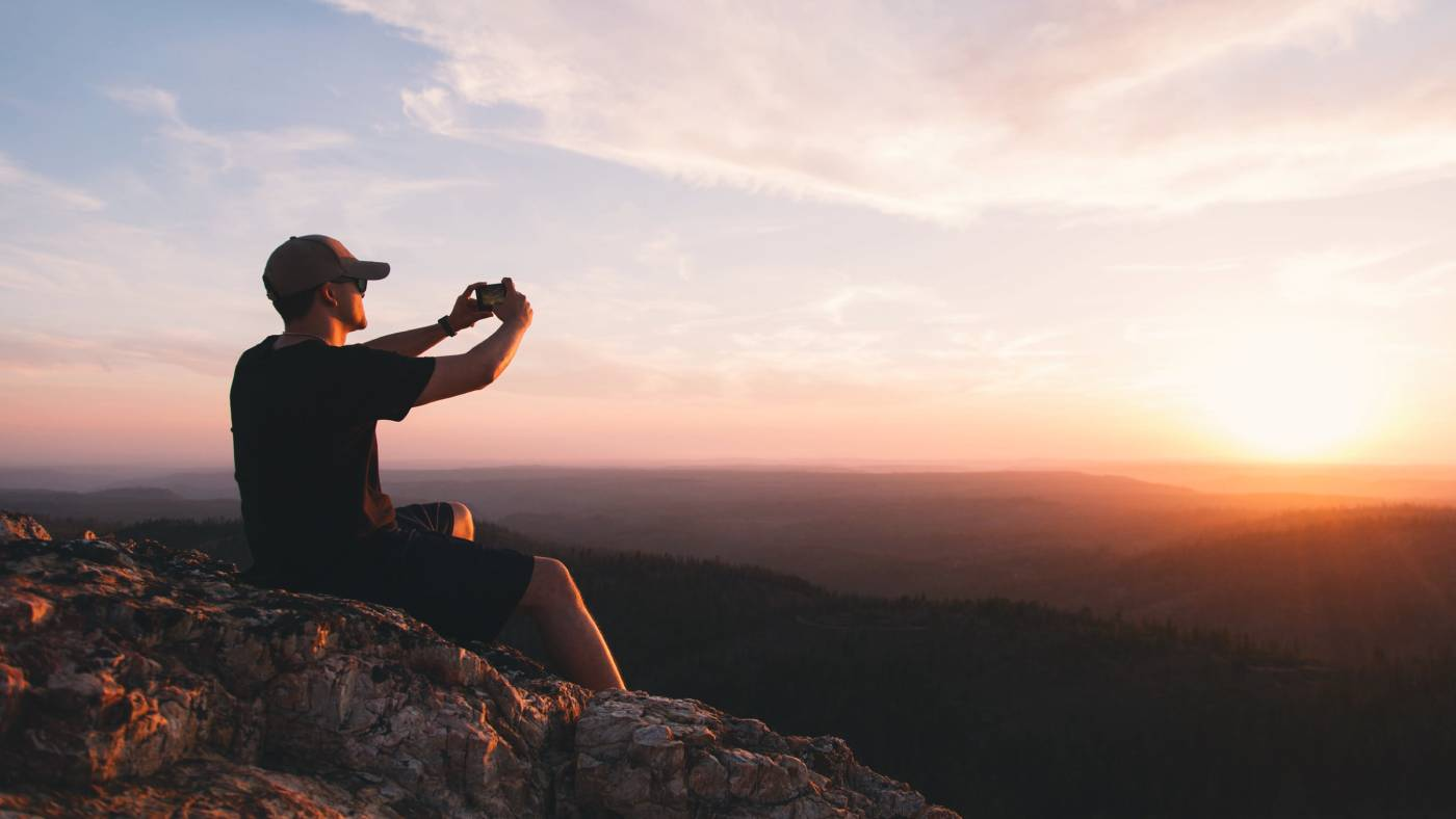 Person shooting sunset with camera