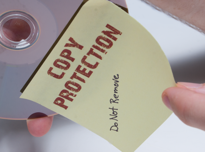 """DVD with a Yellow Post-it note saying """"Copy protection, do not remove"""""""