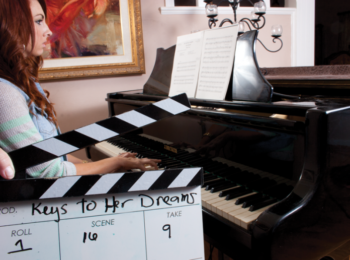Shot of a young woman playing a grand piano.