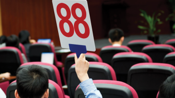 Shot of a man in an auditorium holding up an auction card.