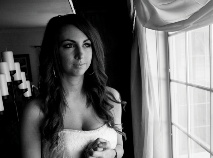 Shot of a bride standing by a window.