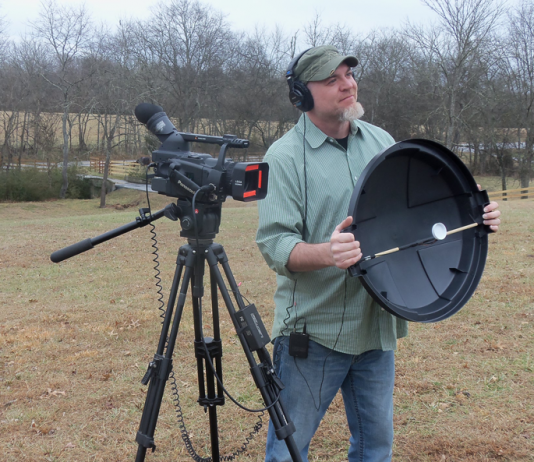 Shot of videographer holding a DIY parabolic mic dish, standing next to a camcorder on a tripod.