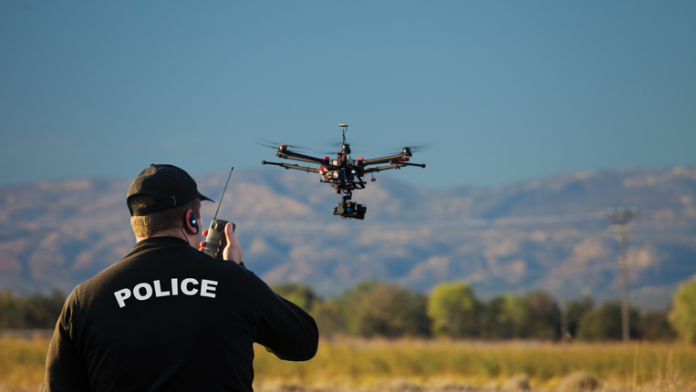 Police officer on radio looking a flying drone.
