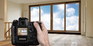 Man shooting empty living room with digital camera