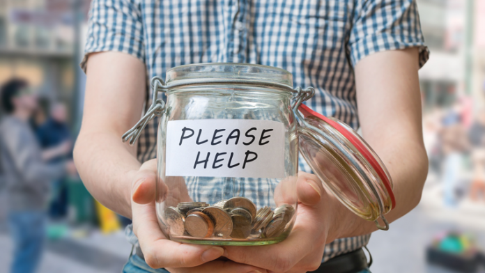 """Person with a donation jar with """"Please Help"""" on it."""