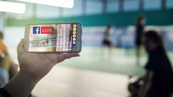 Hand holding a phone live streaming on Facebook Live