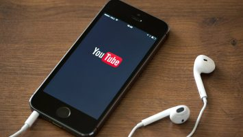 YouTube logo being displayed on a smartphone with earphone plugged into the phone