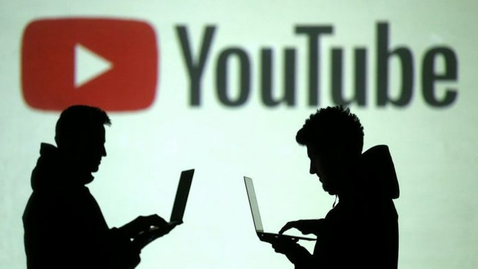 Two silhouetted people working on laptops with the YouTube logo behind them
