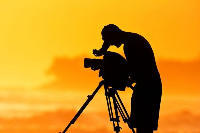 Silhouette of Man with Video Camera at Sunset