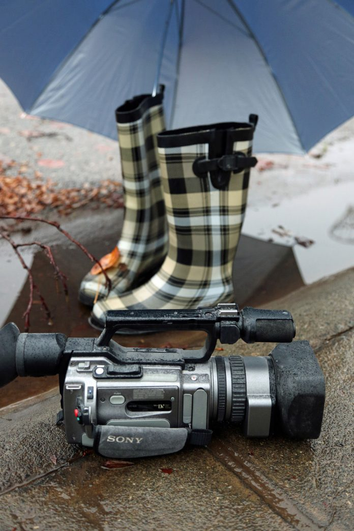 Wet camcorder on rainy street alongside rainboots and covered by an umbrella