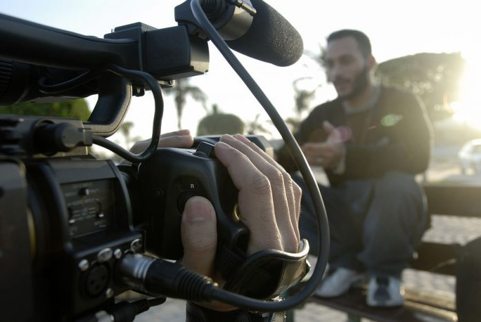 A camera person talks with an interviewee outdoors