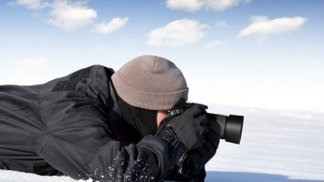 shot of photographer lying in the snow shooting with a camera