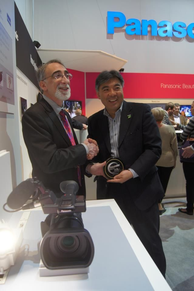 Two people at a tradeshow hold a plaque with a camera in the foreground