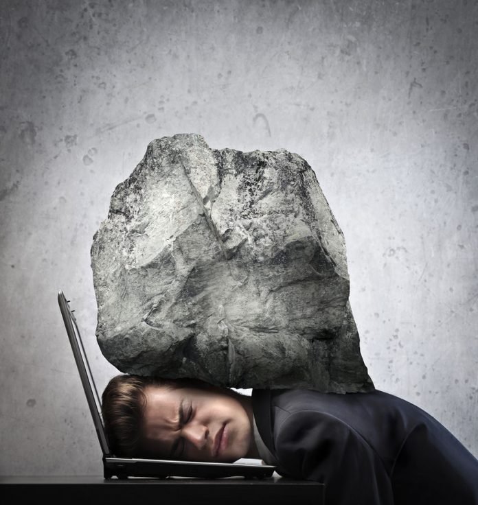 large rock presses down on a business man whose head is on a laptop