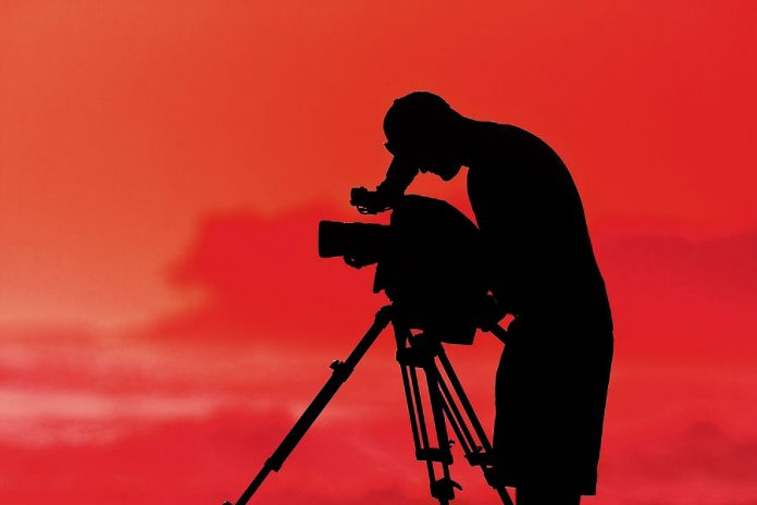 silhouette of a camera operator shooting a scene with a red background