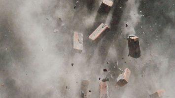 bricks airborne in gray smoke and dust