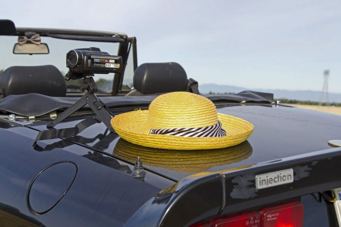 Photo of consumer camcorder sitting on a convertible car ready for a road trip