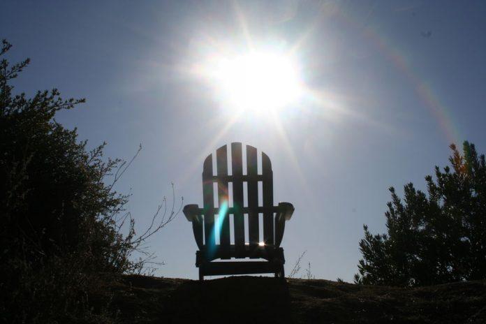Summer sun shining through the slats of a garden chair