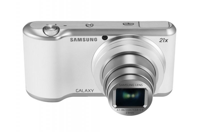white compact camera with lens extending from body