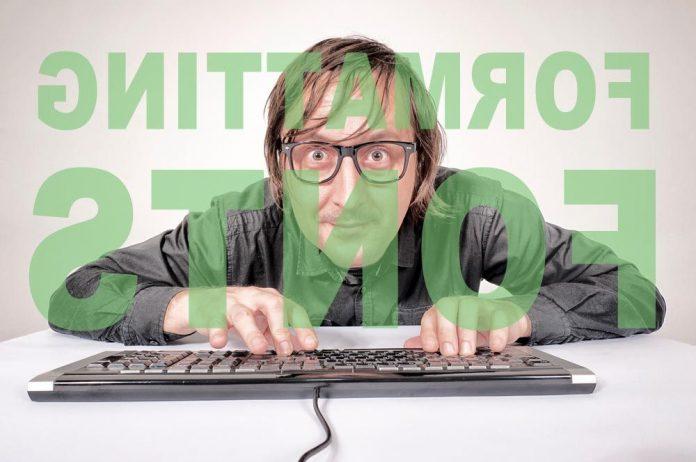 man with glasses at computer keyboard