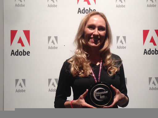 woman with award and Adobe logos in background
