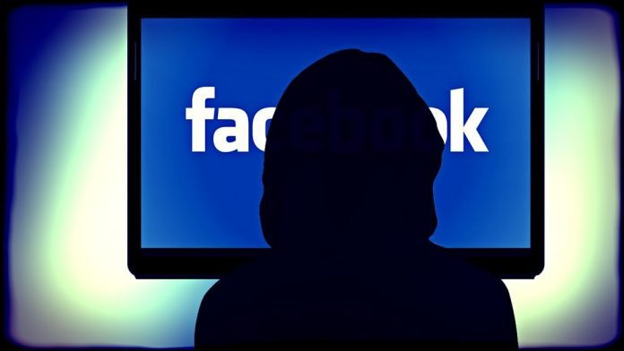 Woman sits in shadow in front of a glowing screen that reads Facebook