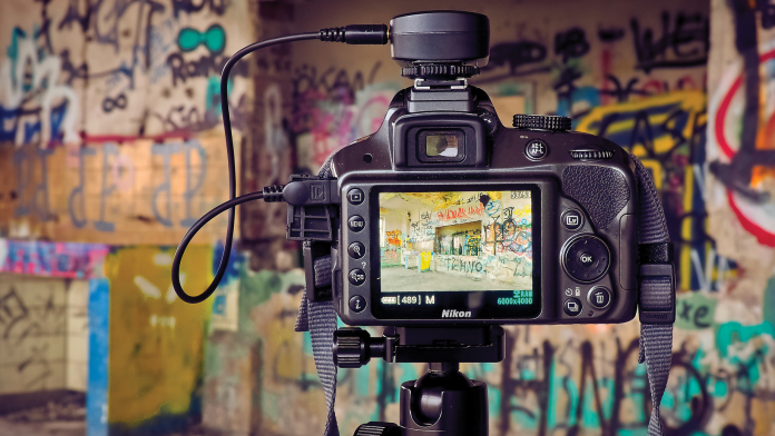 Camera in front of wall filled with graffiti