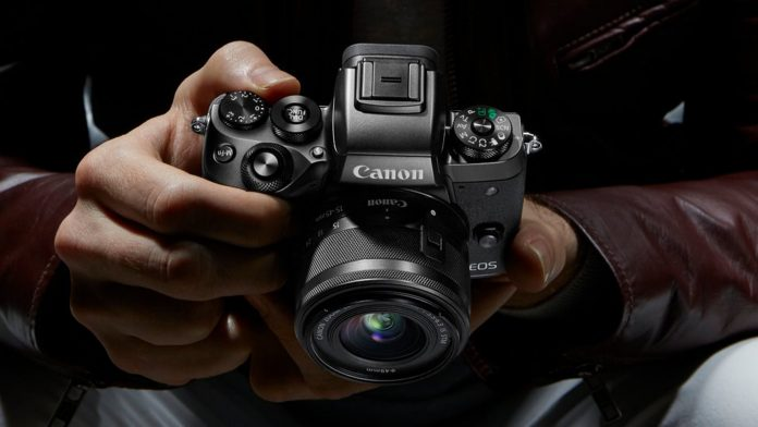 Hands holding a Canon EOS M5 camera