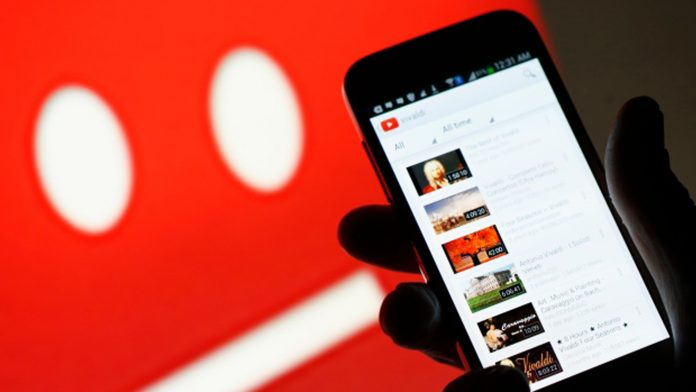Hand holding a  phone that's displaying YouTube videos in front of a background with YouTube's sad face icon